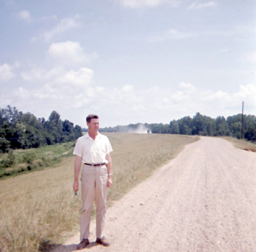 Bill on a country road with combine raising dust